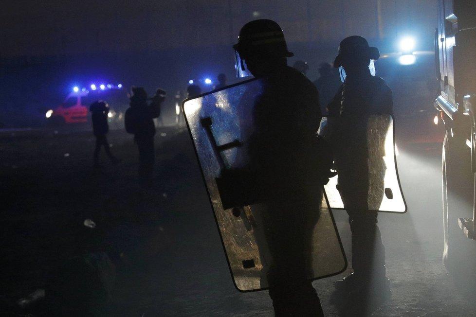 Policisté zasahují proti migrantům, kteří založili požár v táboře v Calais.