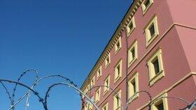 Kolem věznice je natažený žiletkový drát.