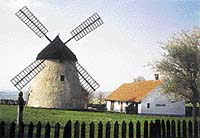 Větrný mlýn holandského typu v Kuželově. Proti větru se natáčí střecha s křídly, zbytek stavby je pevný