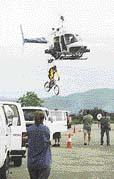 Profesionální cyklista se nechá připojit k vrtulníku, který ho vzduchem dopraví až na rampu, po níž se cyklista řítí vstříc propasti. Následuje střih a nad propastí už otvírá padák kaskadér