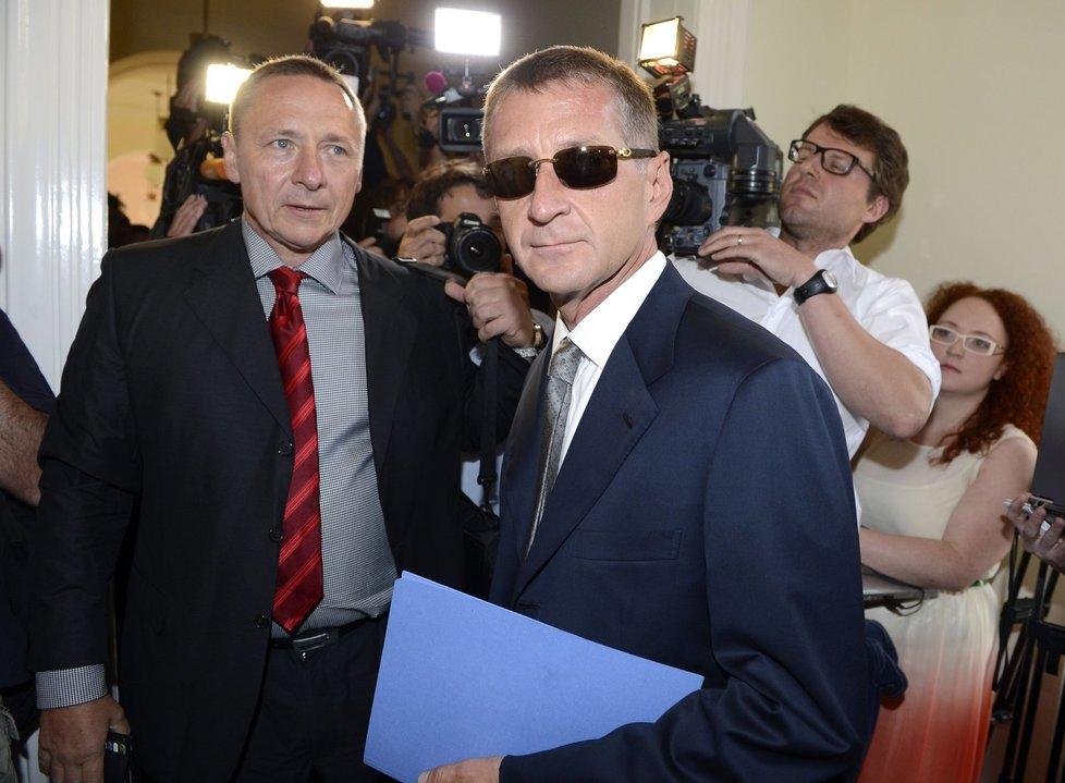 Pohled rozpolceného chlapa kryl lobbista Janoušek, jenž nuceně vyměnil vilu v Chorvatsku a idylu na jachtě za stání u soudu, černými skly značkových brýlí, které image Kmotra v hollywoodském stylu jen pečetily.