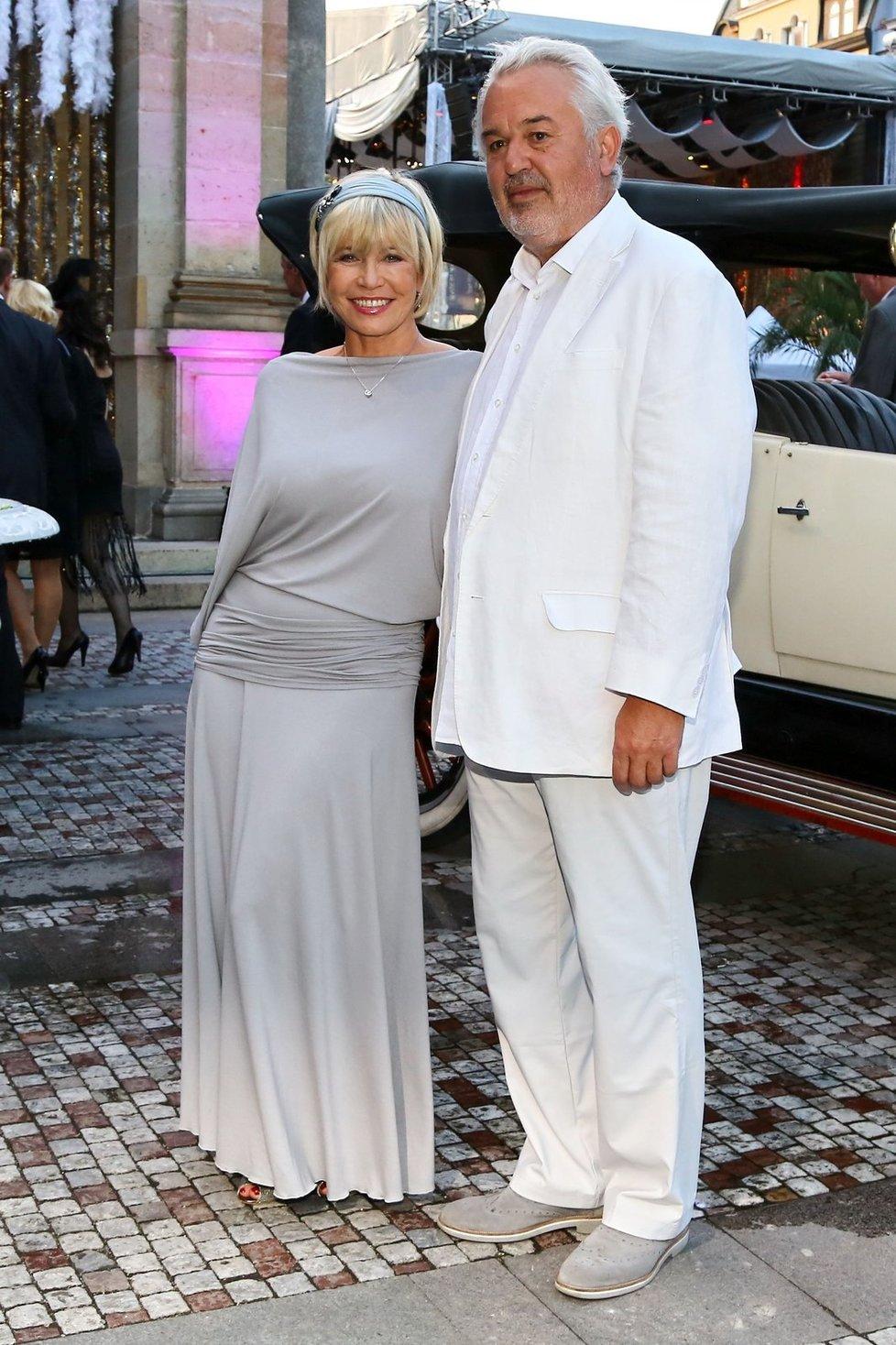 Jana Švandová a Pavel Satorie Bílý oblek je vždy ošemetný, zejména pokud monolit umocňuje stejně barevná košile. Ale bělovlasý podnikatel takovou volbu unese. Jistě i díky šedým střevícům a zejména faktu, že skvěle ladí se svou chotí, neboť ona je v páru za hvězdu. I tato herečka patřila k hrstce žen, jež si uměly s módní epochou Velkého Gatsbyho, jež byla námětem jedné ze zásadních party Filmového festivalu ve Varech, poradit. Sivý odstín podtrhuje kultivovanost střízlivé, ke krku uzavřené kreace s dlouhými rukávy, jež staví na nosnosti krásně padnoucí látky a důmyslné práci s ní.