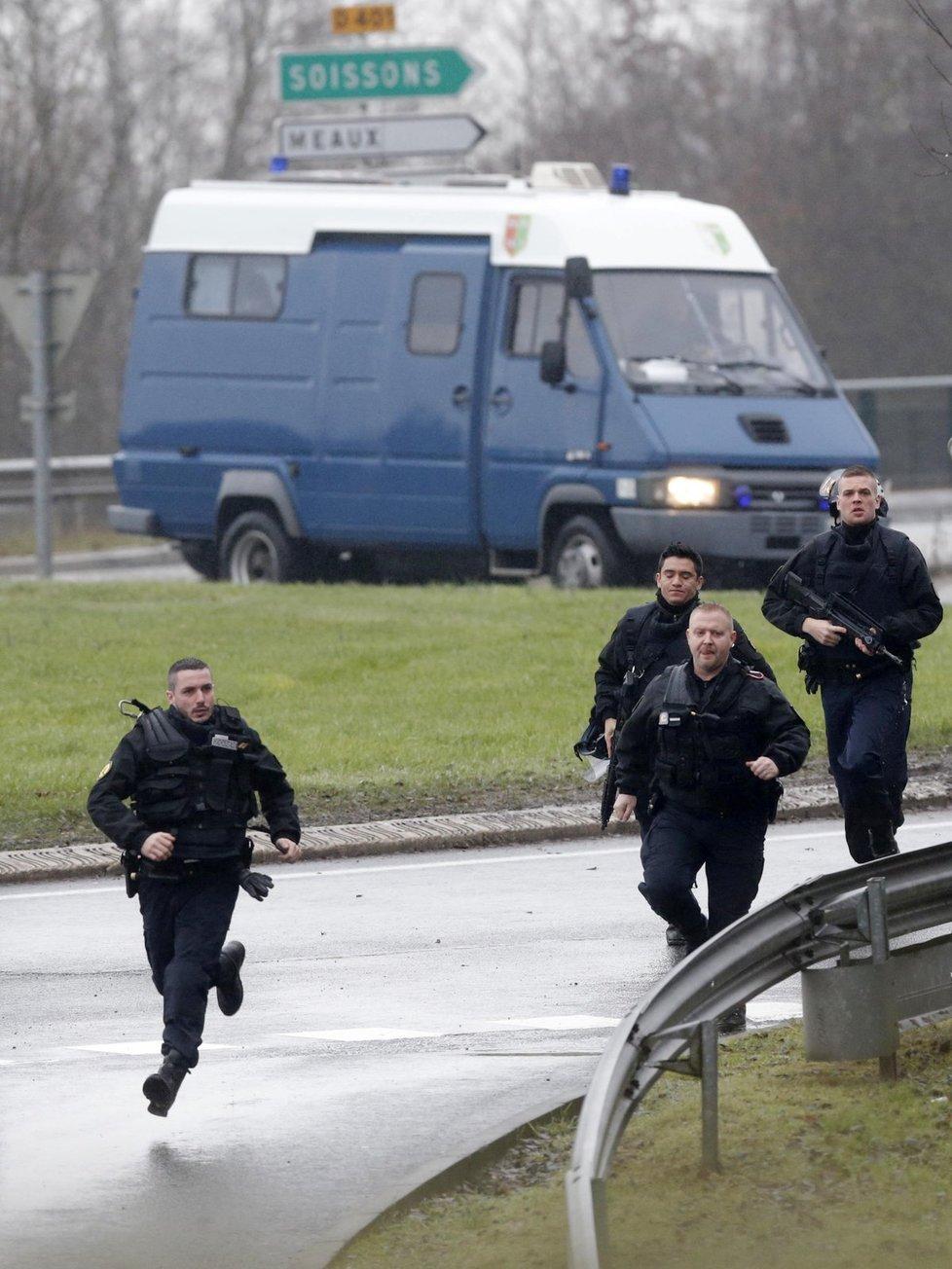 Francouzští policisté běží k budově, kde se zabarikádovali teroristé, kteří vzali rukojmí