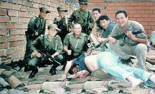 Policisté pózují nad mrtvolou zastřeleného Pabla Escobara.