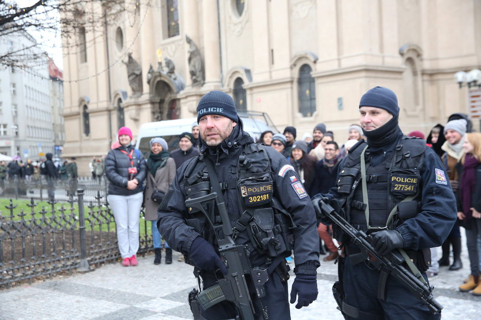 Po trzích na Staroměstském náměstí v Praze se procházejí policisté se samopaly.
