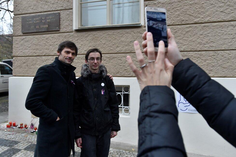 Lékař a prezidentský kandidát Marek Hilšer (vlevo) pózuje pro mobilní fotografii na pražském Albertově, kde spolu s dalšími lidmi uctil 17. listopadu státní svátek u památníku, který připomíná, že právě odtud vyšel 17. listopadu 1989 pochod studentů na Národní třídu.