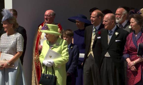 Královna Alžběta II. sleduje odjezd Harryho s Meghan.