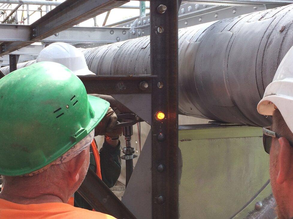 Umísťování žhavého nýtu do konstrukce lávky železničního mostu mezi Výtoní a Smíchovem
