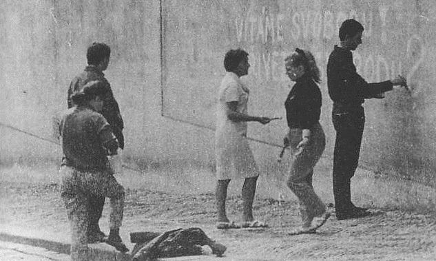 Lidé na ulici malují hesla - běžný pohled srpnových dní a nocí roku 1968.