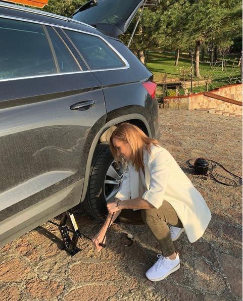 Hana Mašlíková si v bílém saku musela poradit s výměnou pneumatiky.
