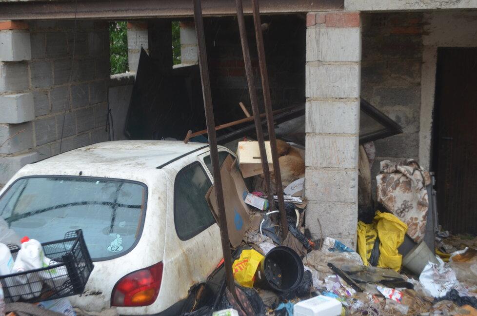Kolem domu je neskutečný nepořádek, mezi odpadky tam žije pes, několik koček a drůbež