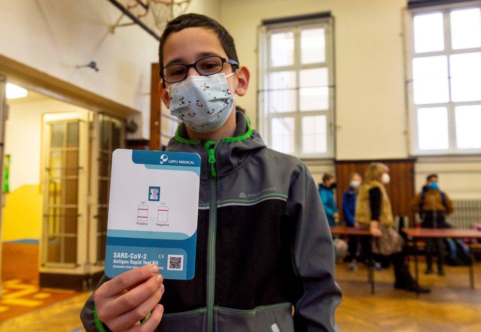 Žák základní školy Chabařovice na Ústecku ukazuje v tělocvičně školy výsledek testu na koronavirus. Vláda rozhodla, že žáci prvního stupně základních škol se od tohoto dne vrátí do lavic v rotační formě, ve školách je jen polovina žáků (12. 4. 2021).