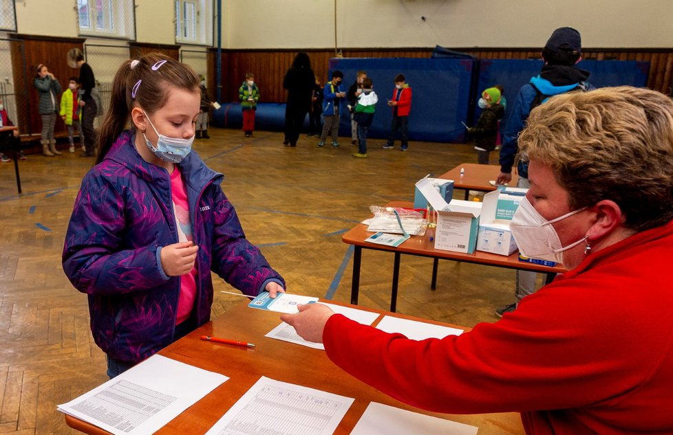 Žákyně základní školy Chabařovice na Ústecku ukazuje zdravotnici v tělocvičně školy výsledek testu na koronavirus. Vláda rozhodla, že žáci prvního stupně základních škol se od tohoto dne vrátí do lavic v rotační formě, ve školách je jen polovina žáků (12. 4. 2021).