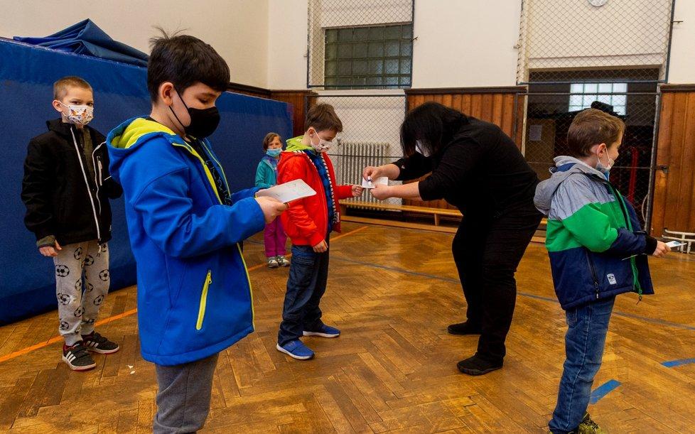 Ředitelka základní školy Chabařovice na Ústecku Dagmar Brožová (druhá zprava) provádí s žáky v tělocvičně školy testy na koronavirus. Vláda rozhodla, že žáci prvního stupně základních škol se od tohoto dne vrátí do lavic v rotační formě, ve školách je jen polovina žáků (12. 4. 2021).