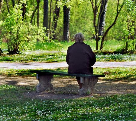 stará žena sedí na lavičce