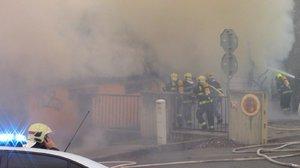 Prosek zahalil hustý dým. Hořela garáž i chatka, teplo poškodilo také vůz