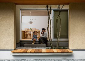 Dřevěný dům s atriem, které zdobí oblázky a vzrostlý strom