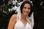 Eva  ve svatebních šatech vystavuje bříško a podvazek