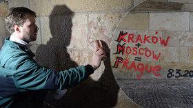 Vandal posprejoval Karlův most: Do podloubí naběhli pracovníci s kartáči, nápis během pár hodin zmizel