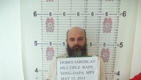 """Guru Jára po zatčení. Policista před ním drží cedulku s nápisem """"Dobeš Jaroslav, mnohonásobné znásilnění"""""""