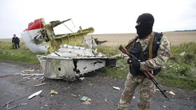 Proruský separatista hlídá trosky letadla.