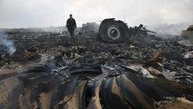 Záchranář uprostřed ohořelého vraku letadla.