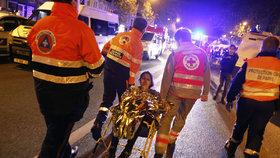 Před klubem Bataclan záchranáři evakuují jednoho z návštěvníků.