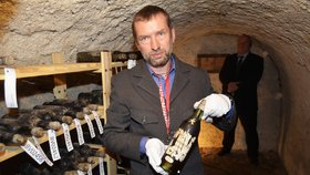 """Kastelán zámku Bečov Tomáš Wizovský ukazuje v depozitáři jednu láhev vína z """"tekutého pokladu""""."""