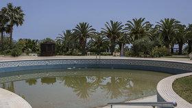 V bazénu stojí zelená voda a okolí zeje prázdnotou.