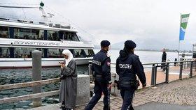 Policisté míjí ženu v hidžábu.