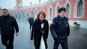 Sobčaková v doprovodu policisty odchází poté, co ji útočník polil vodou a srazil na zem.