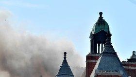 Více než stovka hasičů bojuje s požárem luxusního hotelu v centru Londýna. Ze střechy budovy stoupá hustý dým.