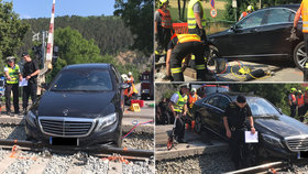 Mercedes uvízl na kolejích. Vyprostit ho museli hasiči.