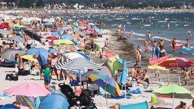 Na německých plážích u Baltského moře se lidé sluní a koupou.