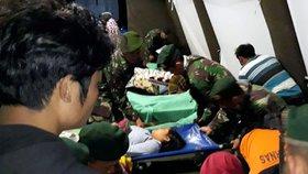 Voják se v polní nemocnici v Lomboku sklání nad ženou zraněnou při zemětřesení v Indonésii.