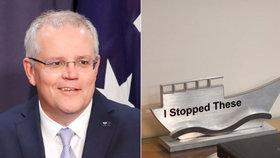 """Australský premiér má na stole zvláštní trofej, naráží na jeho postoj k nelegálním migrantům. """"Tyhle jsem zastavil,"""" hlásá plaketka ve tvaru asijské rybářské lodi."""