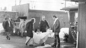 Policisté z Gacyho domu vynášejí těla jeho obětí.
