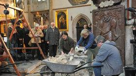 Archeologové opatrně odstraňují vrstvu více než stoleté malty, aby se dostali ke klenbě hrobky.