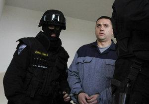 Po zuby ozbrojená eskorta přivádí šéfa vyděračského gangu k soudu.