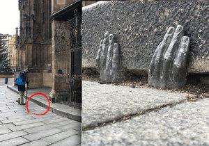 Kovová plastika rukou je na obrubníku katedrály sv. Bartoloměje u mříže s andílky.