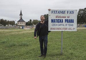 Fotograf David Těšínský s cedulí.