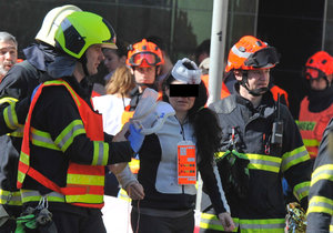 Hasiči odvádějí ženu zraněnou při srážce trolejbusu s tramvají