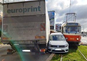 Kuriózní nehoda ve Vysočanech: Auto zůstalo zaklíněné mezi tramvají a náklaďákem, jeden zraněný