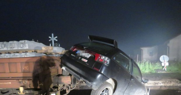 Řidič vjel na rozkopaný železniční přejezd: S autem skončil na odstaveném vagonu