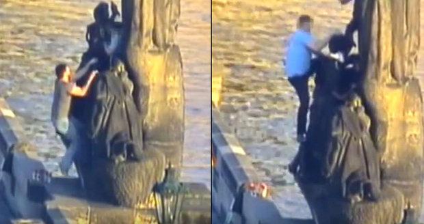 Skupina cizinců šplhala na sochu na Karlově mostě.