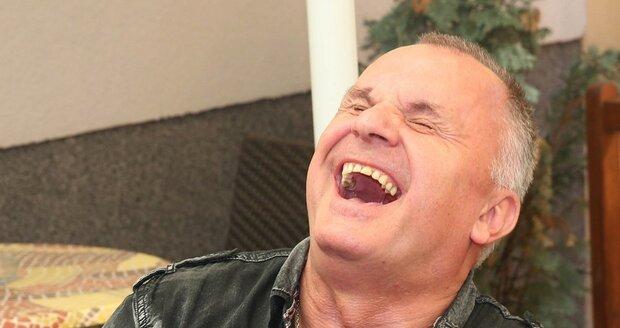 Jožo Ráž se po sklence směje.