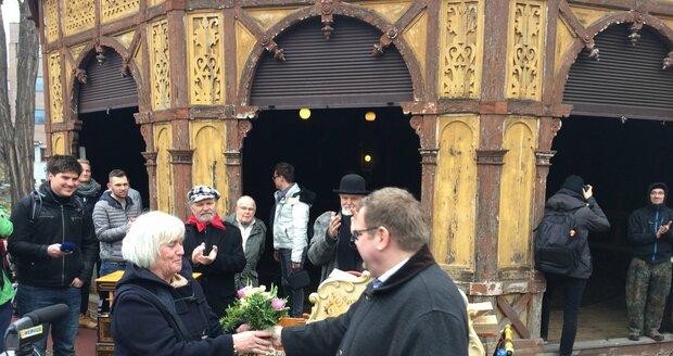 Ředitel muzea Karel Ksandr předává květiny Jarmile Slabé, která pomohla realizovat opravu kolotoče v 90. letech.