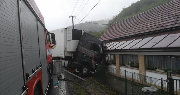 Kamion zůstal zaklíněný v domě po bouračce s autem. Řidič osobáku zemřel