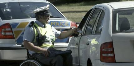 Jan Potměšil coby policajt na vozíku kontroluje řidičům doklady.
