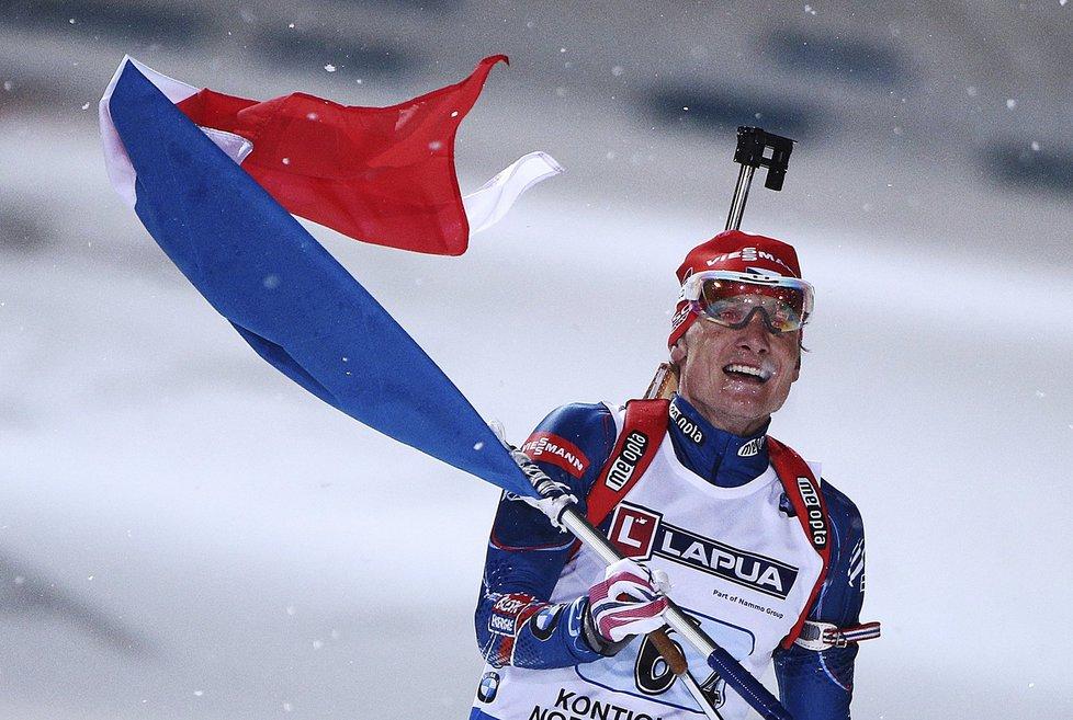 Biatlonista Ondřej Moravec s českou vlajkou přijíždí do cíle závodu smíšených štafet na MS v Kontiolahti